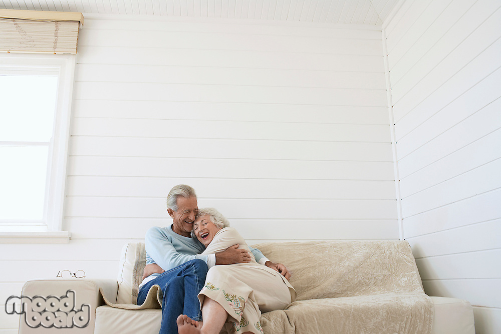 Senior couple embracing sitting on couch in living room