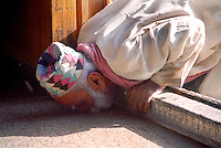 Pakistan, Sehwan Sharif, 2004. A devotee kisses the floor within the shrine of Hazrat Lal Qalander. Anointing himself with a fragrant oil sold inside, he sat quietly in the morning cool for some time.