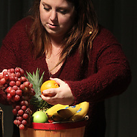 Carra Cockrell makes a fruit basket with different asortments fruit for the holidays.