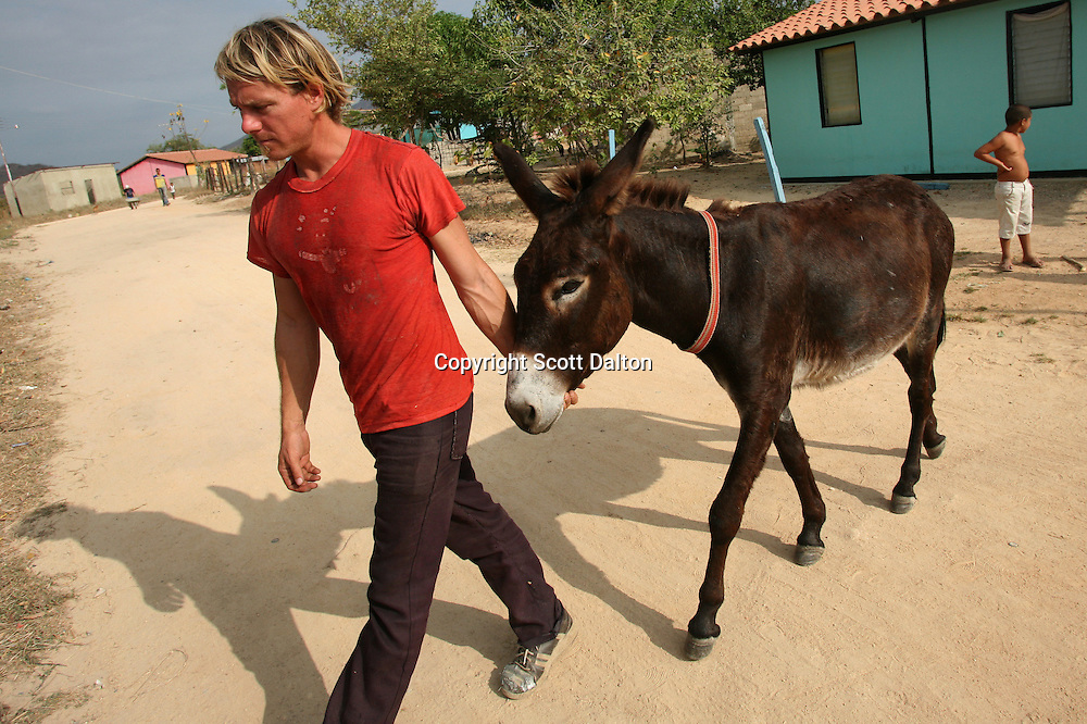 Jonathan Dunham, 33, of Laramie, Wyoming walks with his donkey that he calls Whothey in English but Judas in Spanish, in a poor barrio in Tinaco, Venezuela on Sunday, February 10, 2008. Durham has been walking for the past two years, starting in Oregon. In Mexico he was given the donkey with which he has made the rest of the trek. He plans to continue walking to the tip of Argentina. (Photo/Scott Dalton).