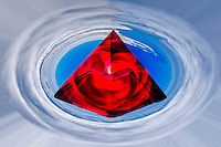 rubedo symbolic representation with red crystal pyramid inside a clouds vortex in the sky