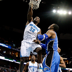 January 27, 2012; New Orleans, LA, USA; New Orleans Hornets center Emeka Okafor (50) dunks over Orlando Magic center Dwight Howard (12) during the first half of a game at the New Orleans Arena.   Mandatory Credit: Derick E. Hingle-USA TODAY SPORTS