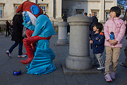 Young foreign tourists hiding behind a sad-looking Smurf character in Trafalgar Square, London.