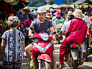 "14 FEBRUARY 2019 - SIHANOUKVILLE, CAMBODIA: A Chinese worker rides his motorcycle through the Leu Market in Sihanoukville. There are thousands of Chinese workers in Sihanoukville who work to support the casino and hotel industry in the town. There are about 80 Chinese casinos and resort hotels open in Sihanoukville and dozens more under construction. The casinos are changing the city, once a sleepy port on Southeast Asia's ""backpacker trail"" into a booming city. The change is coming with a cost though. Many Cambodian residents of Sihanoukville  have lost their homes to make way for the casinos and the jobs are going to Chinese workers, brought in to build casinos and work in the casinos.      PHOTO BY JACK KURTZ"