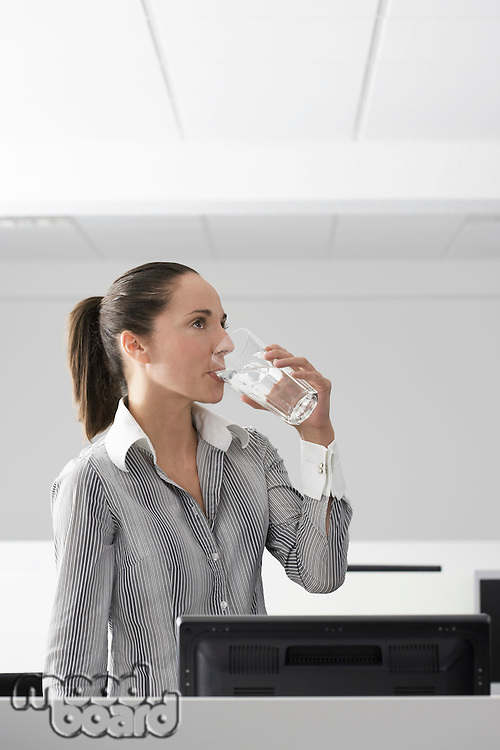 Female office worker drinking water in office cubicle