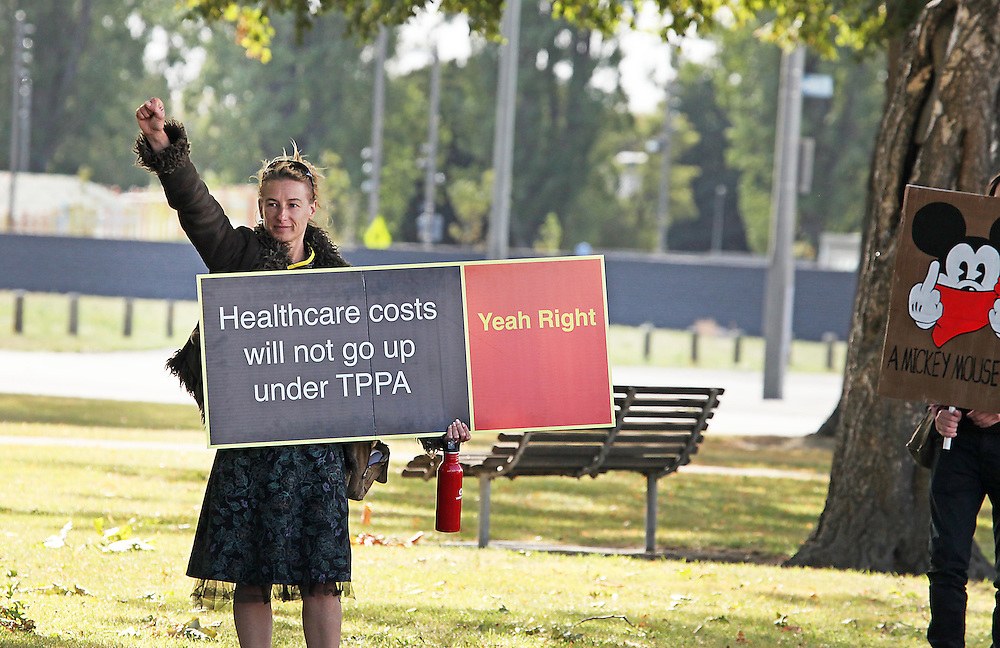 Anti TPPA protesters on Latimer Square outside the Rydges Hotel asking cars to toot to support them, Christchurch, New Zealand, Friday, 11 March, 2016. Credit: SNPA / Pam Carmichael