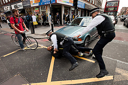 © Licensed to London News Pictures. 11/09/2011. London, UK. Police scuffle with and detain an Muslims Against Crusaders protester on Edgware Road as they are lead back to the Regents Park Mosque following their demonstration. Radical Islamist group, Muslims Against Crusades, hold a protest outside the US Embassy in Grosvenor Square, London, on the 10th anniversary of the September 11th terrorist attacks on America. A counter-protest was held at the same time by the English Defence League. Photo credit : Joel Goodman/LNP