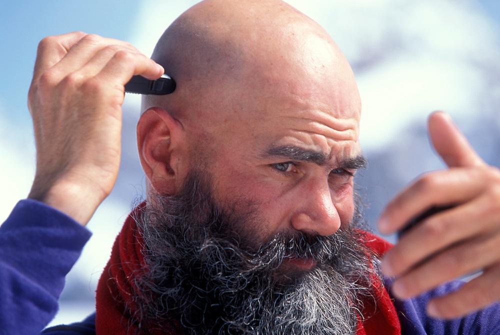USA, Alaska, Denali National Park, (MR) Vern Tejas shaves head at Denali base camp on Mount McKinley.