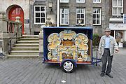 Nederland, Den Bosch, 6-9-2014Een klein draaiorgel staat te spelen op de markt. een oudere man staat met het geldbakje te schudden.FOTO: FLIP FRANSSEN/ HOLLANDSE HOOGTE