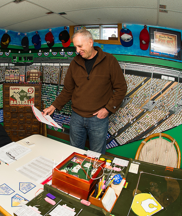 "Bill Colby pulls out the 1971 season his group is currently playing with the Strat-O-Matic game in his ""Fenway Park"" room.  (Karen Bobotas/for the Laconia Daily Sun)"