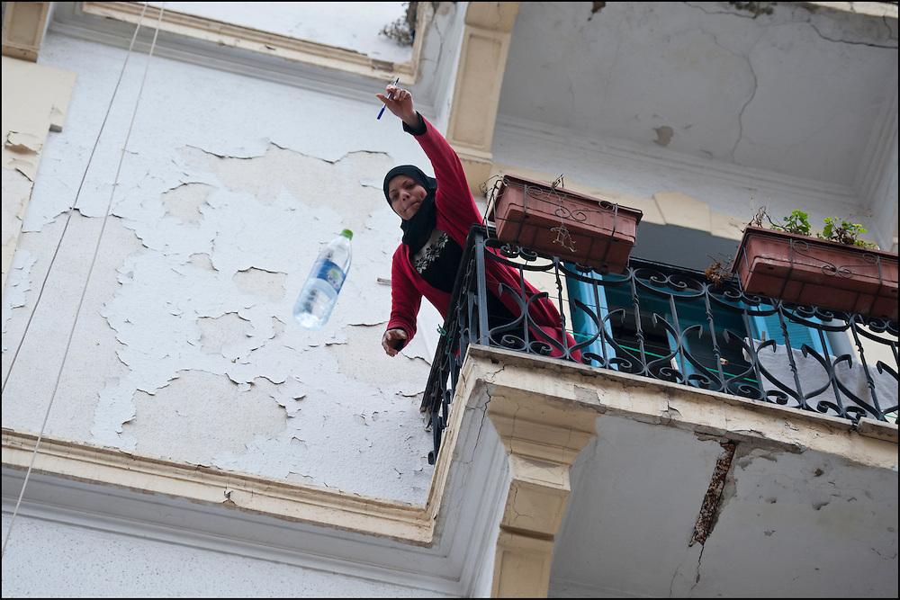 Une Tunisoise offre de l'aide aux manifestants depuis son balcon en leur jetant une bouteille d'eau. // Des affrontements entre la police et les manifestants ont éclaté dans le centre de Tunis, notamment avenue Habib Bourguiba, faisant (selon Associated Press) 3 morts (prétendument par balle) et 12 blessés parmi les manifestants, Tunis le 26 février 2011.