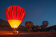 Hot-air balloons and pre-dawn glow at 25th Annual Red Rock Balloon Rally, Red Rock State Park, Gallup, New Mexico.