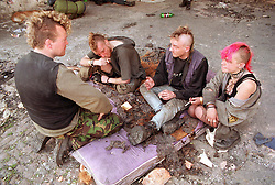 Group of homeless people sitting on floor smoking cigarettes and talking,