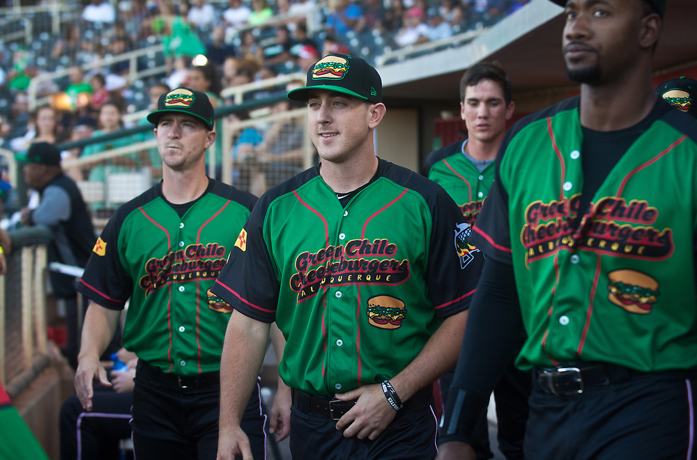 mkb061617a/sports//Marla Brose --  Albuquerque Green Chile Cheeseburgers' Thad Weber, left, Zach Jemiola, second from left, and Domonic Brown, right, get ready to start Friday night's baseball game against the Fresno Tacos, June 16, 2017, at Isotopes Park in Albuquerque, N.M. The  Albuquerque Green Chile Cheeseburgers took the field for one night only.  (Marla Brose/Albuquerque Journal)