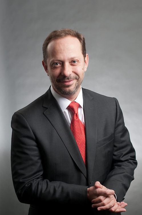 Santander banker headshot in front of solid gray backdrop with light gradient.