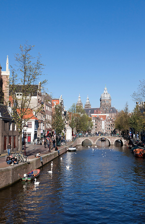 A sunny Sunday afternoon on the Voorburgwal, a scenic canal in Amsterdam's Old Town.