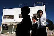 Palestinian children stand in front of a demolished home in the northern West Bank town of Jenin on November 17, 2003...Photo by Erin Lubin