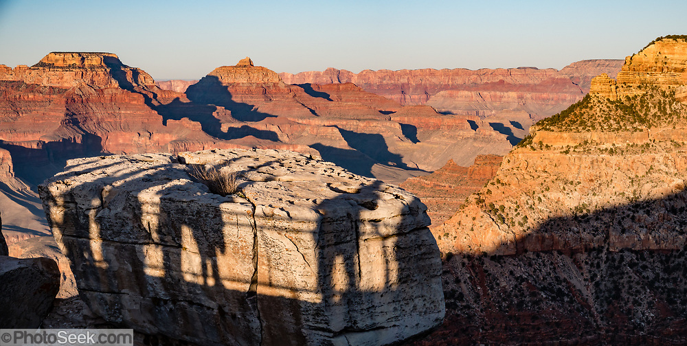 Sunset casts shadows of people at Mather Point Overlook, Grand Canyon National Park, Arizona, USA. Starting at least 5 to 17 million years ago, erosion by the Colorado River has exposed a column of distinctive rock layers, which date back nearly two billion years at the base of Grand Canyon. While the Colorado Plateau was uplifted by tectonic forces, the Colorado River and tributaries carved Grand Canyon over a mile deep (6000 feet), 277 miles  long and up to 18 miles wide. This image was stitched from multiple overlapping photos.