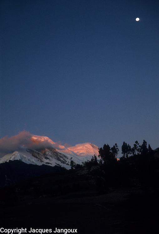 Peru, Andes Montain Range - Cordillera de los Andes, Cordillera Blanca mountain range, dusk on snow-covered slopes of Mount Huascarán (6768 m), highest mountain in Peru, with last rays of sun on top of mountain and moon rising.