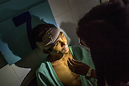 Orlando Chabaria Ribera's is examined by Ana Robles, an intern, at Occidente Hospital in Santa Rosa de Copan, Honduras, March 3, 2014. Ribera was attacked and robbed by machete wielding bandits. He was found by passers by with horse manner packed in a large head wound from the machete. Photo Ken Cedeno