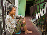 24 FEBRUARY 2015 - PHNOM PENH, CAMBODIA: A woman who lives in the White Building relaxes on a staircase landing. The White Building, the first modern apartment building in Phnom Penh, originally had 468 apartments, and was opened the early 1960s. The project was overseen by Vann Molyvann, the first Cambodian architect educated in France. The building was abandoned during the Khmer Rouge occupation. After the Khmer Rouge were expelled from Phnom Penh in 1979, artists and dancers moved into the White Building. Now about 2,500 people, mostly urban and working poor, live in the building. Ownership of the building is in dispute. No single entity owns the building, some units are owned by their occupants, others units are owned by companies who lease out apartments. Many of the original apartments have been subdivided since the building opened and serve as homes to two or three families. The building has not been renovated since the early 1970s and is in disrepair. Phnom Penh officials have tried to evict the tenants and demolish the building but residents refuse to move out.   PHOTO BY JACK KURTZ