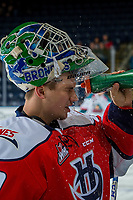 KELOWNA, CANADA - JANUARY 17: Logan Flodell #30 of the Lethbridge Hurricanes stands at the bench during warm up and cools off with water on his face against the Kelowna Rockets on January 17, 2018 at Prospera Place in Kelowna, British Columbia, Canada.  (Photo by Marissa Baecker/Shoot the Breeze)  *** Local Caption ***