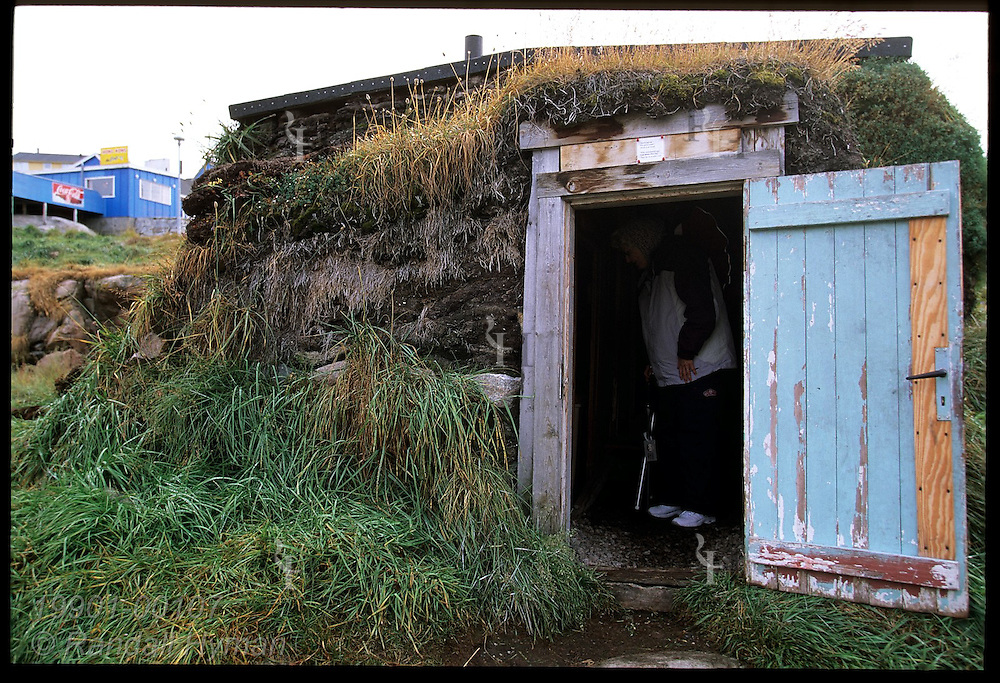 American tourist stands inside a traditional turf home at Knud Rasmussen Museum, birthplace of famed explorer; Ilulissat, Greenland.