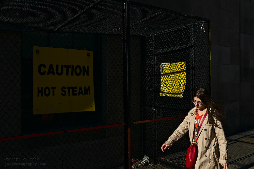 "Woman walking past sign reading, ""Caution Hot Steam"", New York, NY, US"