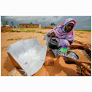 A woman pours tea in a refugee camp in Iridimi in Tchad, close to the sudanese border. The tea is boiled in a solar cooker, fabricated by women in the camp.  More than 23.000 refugees from Darfur, mainly women and children, live in the camp. The benefits of solar cookers are huge: Traditionally women do the hard job of gathering wood for fire. In a barren, conflict ridden area like the Darfur border, the women walk long distances in search of the wood, and are often assaulted and raped. The solar cookers alleviate both the hard work and the dangers facing these women.  The conflict in Darfur with its ethnic cleansing is also a direct result of climate change. Farmers and herders are pitted against each other over diminishing  pasture and resources. The barren land is taken over by the Sahara desert, which has expanded 60 miles over the last 40 years. Rainfall is down by 16-30 percent. Crops are failing. With further global warming, conflicts like Darfur are likely to be repeated on even larger scale.
