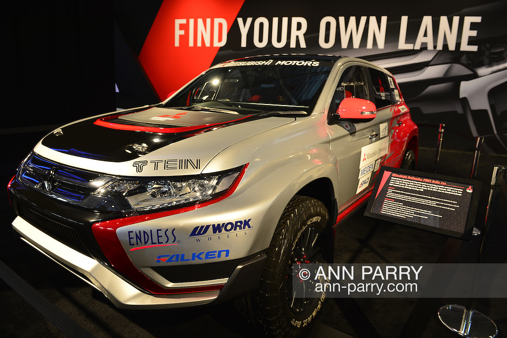 """The Mitsubishi Outlander PHEV Rally Car, with Tein, Endless, Work Wheels, and Falken stickers, is on display with """"FIND YOUR OWN LANE"""" slogan in background at the New York International Auto Show 2016, at the Jacob Javits Center. This was Press Preview Day one of NYIAS, and the Trade Show will be open to the public for ten days, March 25th through April 3rd."""