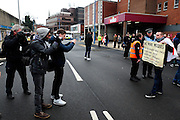 English Defence League (EDL) demonstration<br /> called in protest to the proposed building of a new mosque in Dudley.<br /> A supporter of the English Defence League displaying a poster calling for 'no more mosques' in Dudley, being photographed.