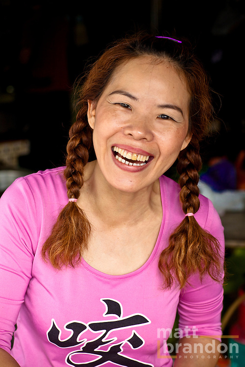 "This Chinese shopkeeper smiles as her photo is taken. Her shirt says in Chinese ""bite""."