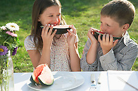 Boy and girl (7-9) sitting at table in garden and eating watermelon