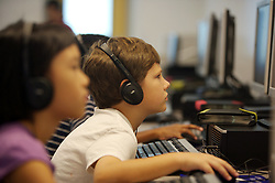 Stock photo of children using headphones working in the computer lab at Lovett Elementary School in Houston Texas