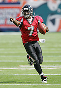 MIAMI - NOVEMBER 6:  Quarterback Michael Vick #7 of the Atlanta Falcons points toward Miami Dolphins defenders as he rolls out on a running play on November 6, 2005 at Dolphins Stadium in Miami, Florida. The Falcons defeated the Dolphins 17-10. ©Paul Anthony Spinelli *** Local Caption *** Michael Vick
