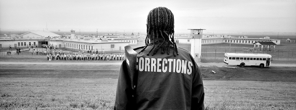 Mary Bloomer, a prison security guard, watches from the levee as prisoners form Field Line 15 from Wolf Dormitory at Camp C at Angola, Louisiana's maximum security prison. Angola is a massive top-security prison, occupying flat delta land equal to the size of Manhattan.  Prisoners walk or ride in buses to and from their jobs every day.