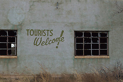 abandoned building with tourists  welcome sign painted on the decayed walls