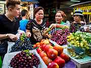 "18 MAY 2017 - BANGKOK, THAILAND: People buy fresh fruit at a street food stall in Bangkok's Chinatown. City officials in Bangkok have taken steps to rein in street food vendors. The steps were originally reported as a ""ban"" on street food, but after an uproar in local and international news outlets, city officials said street food vendors wouldn't be banned but would be regulated, undergo health inspections and be restricted to certain hours on major streets. On Yaowarat Road, in the heart of Bangkok's touristy Chinatown, the city has closed some traffic lanes to facilitate the vendors. But in other parts of the city, the vendors have been moved off of major streets and sidewalks.      PHOTO BY JACK KURTZ"