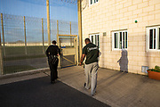 A prisoner is escorted through a locked gate by an officer back to his wing. HMP/YOI Portland, Dorset. A resettlement prison with a capacity for 530 prisoners. Portland, Dorset, United Kingdom.