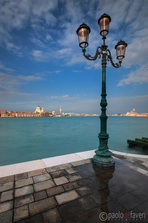 A very typical Venetian view, a simple, geometrical composition: a quay and a lamp post on the Giudecca right in front of the Redentore church, and the strip of buildings of downtown Venice in the background.