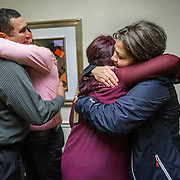 FAIRFAX, VA -DEC21: Emerita Ayala gets a hug from her mother Zenayda while her dad Martin, hugs her new husband Josue Alvarenga, during their wedding at the law office of Jose Aunon, in Fairfax, Virginia, December 21, 2016. Emerita graduated from college in the morning, and got married the same afternoon. Emerita started college as a teenage mom at 18, with her 3-year-old son at community college. She got help through a nonprofit called Generation Hope that provides scholarships and mentoring to teenage moms, and earned her bachelors degree from George Mason University. (Photo by Evelyn Hockstein/For The Washington Post)