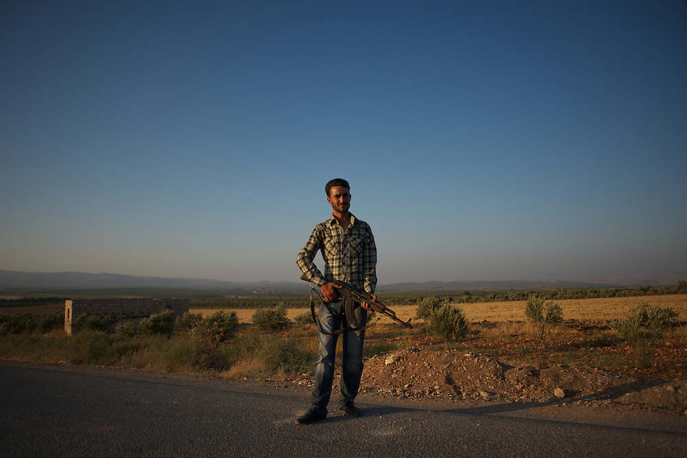 August 12, 2012 - Kafa Safra, Efrin, Syria: A Kurdistan Workers' Party (PKK) fighter takes guard at a checkpoint outside the village of Kafra Safra...PKK has been fighting an armed struggle against the Turkish state for an autonomous Kurdistan and greater cultural and political rights for the Kurds in Turkey, Iraq, Syria and Iran. Founded on 27 November 1978 in the village of Fis, was led by Abdullah Öcalan. The PKK's ideology was originally a fusion of revolutionary socialism and Kurdish nationalism - although since his imprisonment, Öcalan has abandoned orthodox Marxism. The PKK is listed as a terrorist organization by Turkey, the United States, the European Union and NATO. (Paulo Nunes dos Santos)