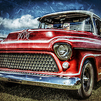 Vintage retro classic pickup truck in red under stormy sky with texture and grain