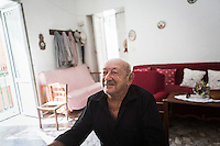 ACCIAROLI (POLLICA), ITALY - 5 OCTOBER 2016:  94-years-old Giuseppe Vassallo sits in the living room of his house in Acciaroli, a hamlet in the municipality of Pollica, Italy, on October 5th 2016. Giuseppe Vassallo was an Italian Navy official during WWII. At age 86, 8 years ago, Mr Vassallo had multiple sex affairs to overcome his depression following his wife's death. He was a testimonial of the Acciaroli's mediterranean  diet and lifestyle during Expo 2015, the Universal Exposition hostel in Milan last year.<br /> <br /> To understand how people can live longer throughout the world, researchers at University of California, San Diego School of Medicine have teamed up with colleagues at University of Rome La Sapienza to study a group of 300 citizens, all over 100 years old, living in Acciaroli (Pollica), a remote Italian village nestled between the ocean and mountains in Cilento, southern Italy.<br /> <br /> About 1-in-60 of the area's inhabitants are older than 90, according to the researchers. Such a concentration rivals that of other so-called blue zones, like Sardinia and Okinawa, which have unusually large percentages of very old people. In the 2010 census, about 1-in-163 Americans were 90 or older.