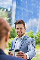 Portrait of young attractive businessman giving coffee to businesswoman
