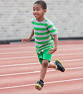 Middletown, New York - A young boy competes in a race during the Twilight Track and Field Series run by the Middletown High School Varsity track program on July 22, 2014. ©Tom Bushey / The Image Works