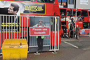 Footpath disruption sign using illustration of TFL workman, with background of Victoria buses.