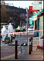 Two forensic experts walk past police clothing and a medics bag as they enter the Halal Butchers in Kingsbury where a man on the rampage attacked 4 police officers, stabbing 3 of them, Saturday Nov. 19, 2011. Photo by Morn/ i-Images