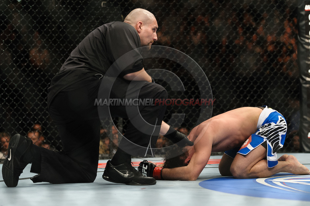 "BIRMINGHAM, ENGLAND, NOVEMBER 5, 2012: Referee Leon Roberts checks on a downed Brad Pickett during ""UFC 138: Munoz vs. Leben"" inside the National Indoor Arena in Birmingham, United Kingdom"