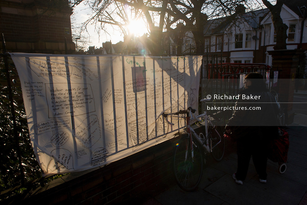 A sunlit banner on the railings of Carnegie Library in Herne Hill, south London while occupiers remain inside the premises on day 5 of its occupation, 4th April 2016. The angry local community in the south London borough have occupied their important resource for learning and social hub for the weekend. After a long campaign by locals, Lambeth have gone ahead and closed the library's doors for the last time because they say, cuts to their budget mean millions must be saved. A gym will replace the working library and while some of the 20,000 books on shelves will remain, no librarians will be present to administer it.
